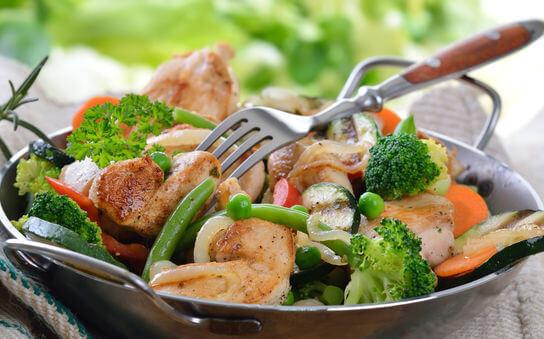 Gebratenes Hühnerfilet mit Mischgemüse in der Servierpfanne